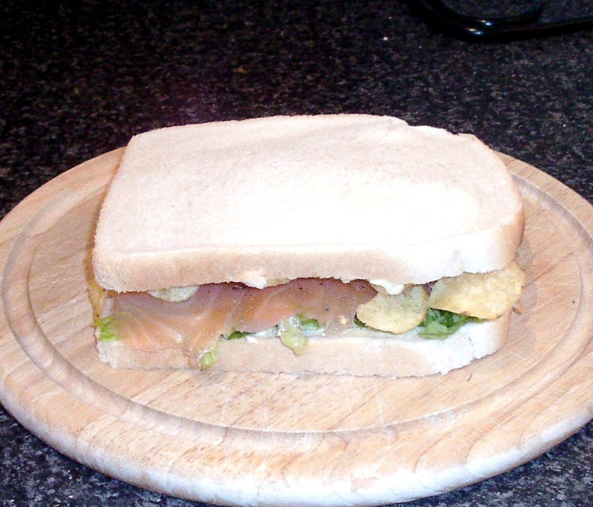 Top is placed on smoked salmon, salad and crisps sandwich