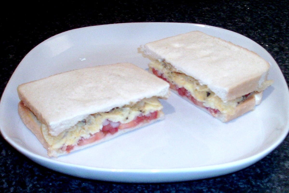 Cheese melted over tomato and red onion topped with ready salted crisps sandwich