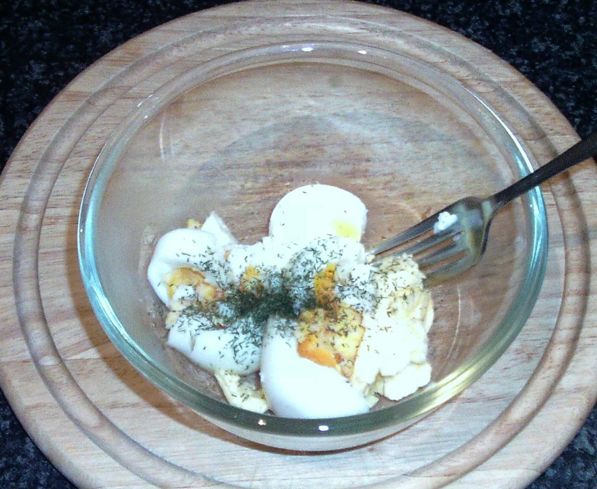 Mashing eggs, butter and seasoning