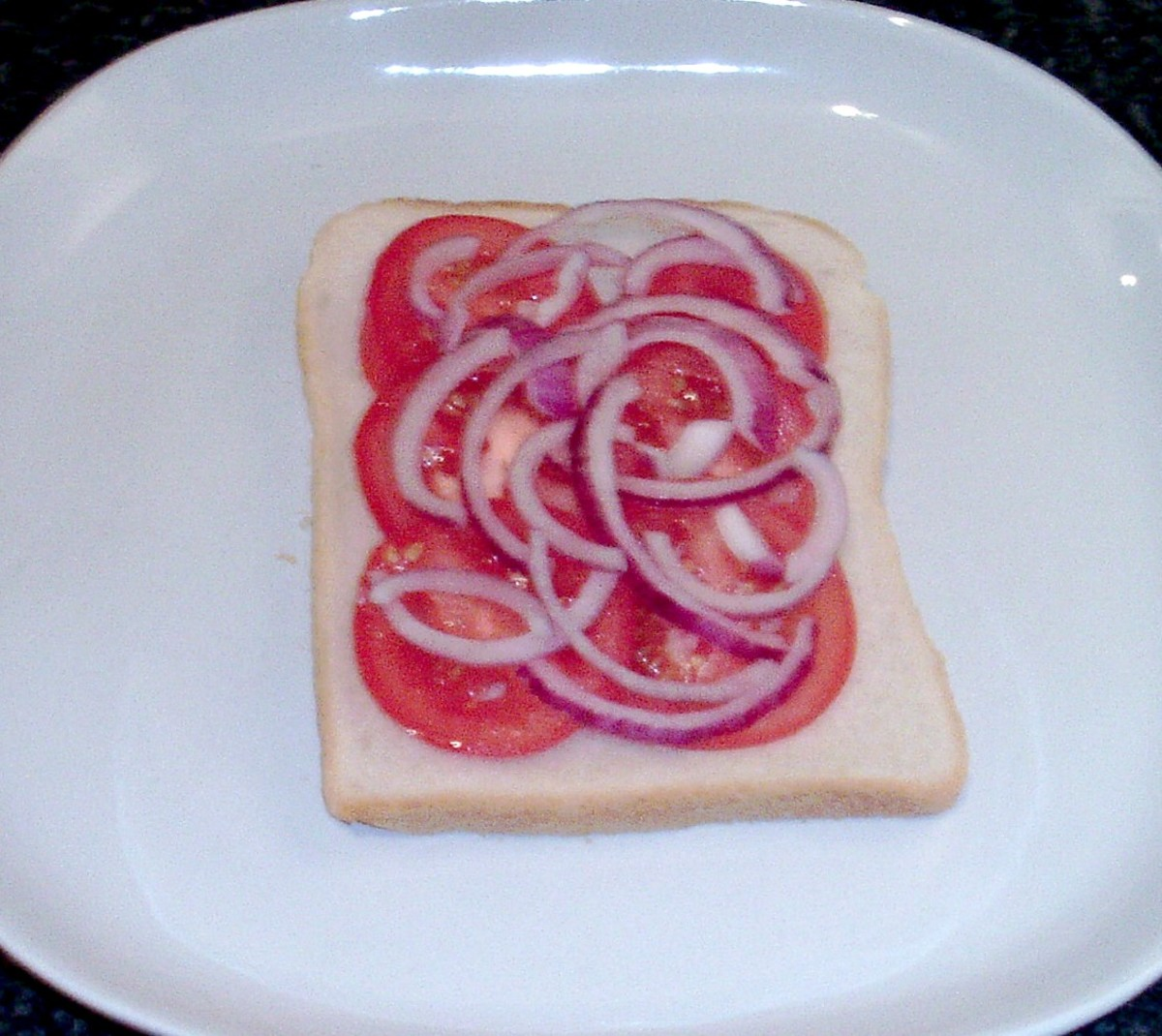 Red onion strands top tomato