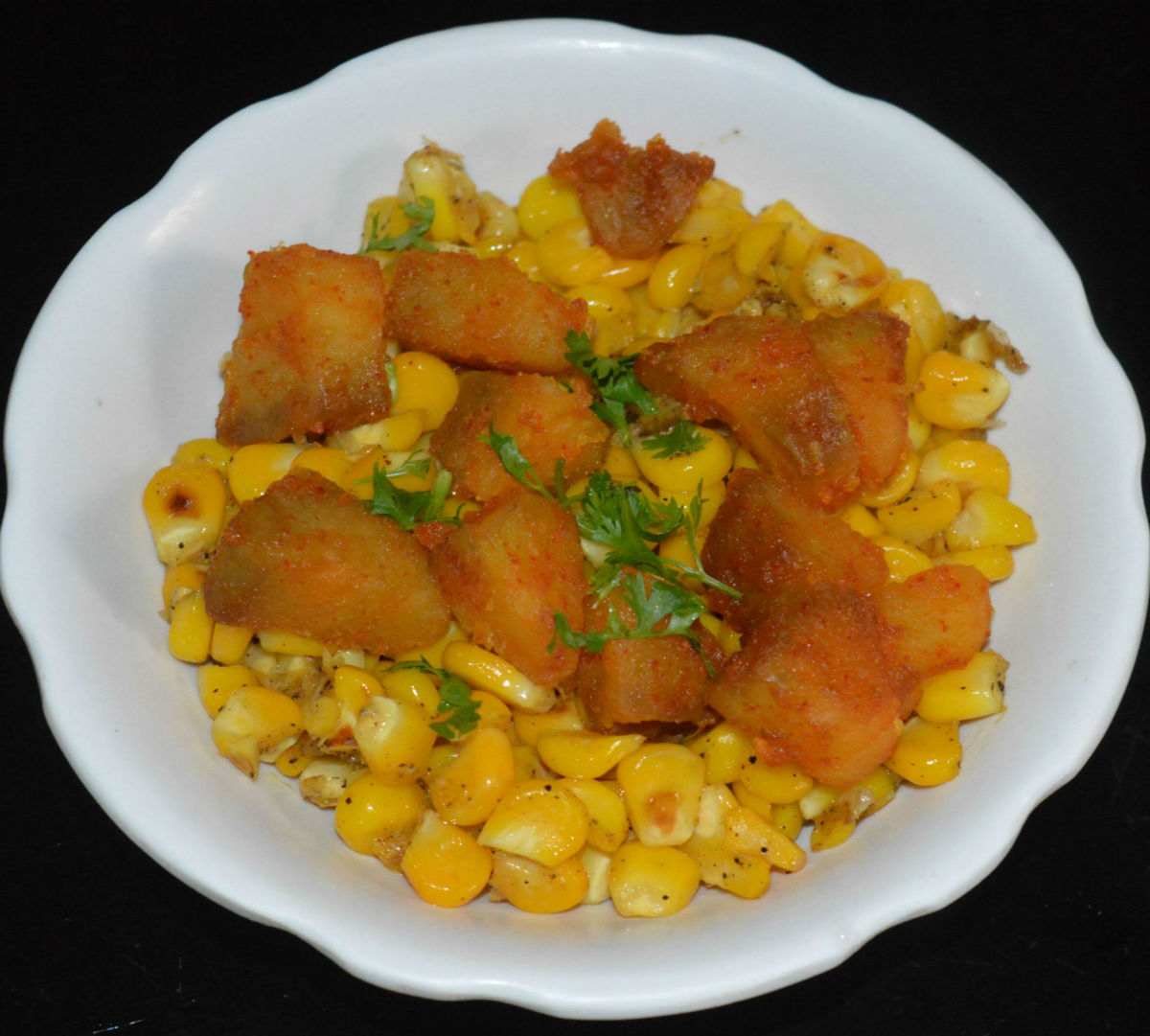 Step seven: Add this corn equally into two bowls. Top them each with half portion of cooked spicy potatoes. Garnish it with finely chopped green coriander leaves.
