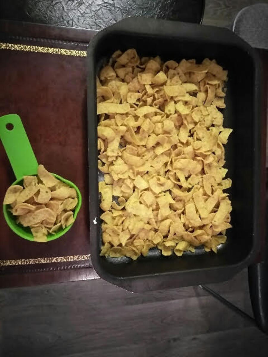 One cup of Fritos is reserved for the topping (left) and the rest of the Fritos line the bottom of the baking pan (right).
