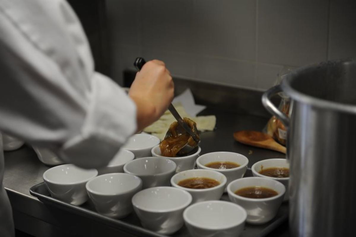a chef ladling soup into bowls
