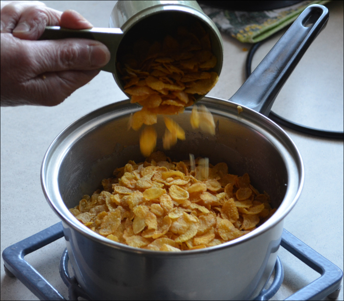Corn Flakes being added to frothing ingredients to make the Honey Joy Biscuits.