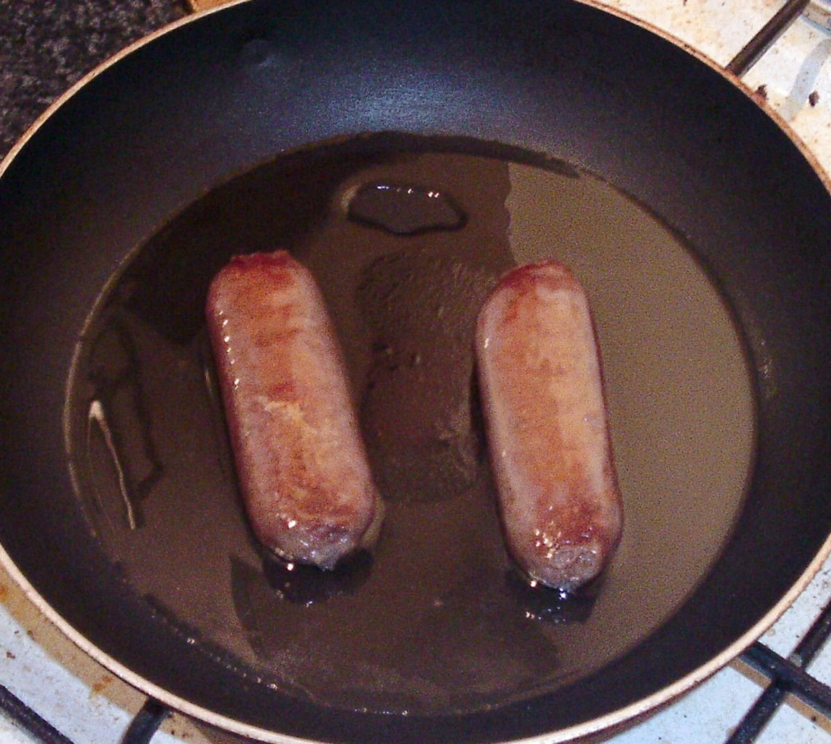 Venison sausages should be turned frequently as they are gently shallow fried.