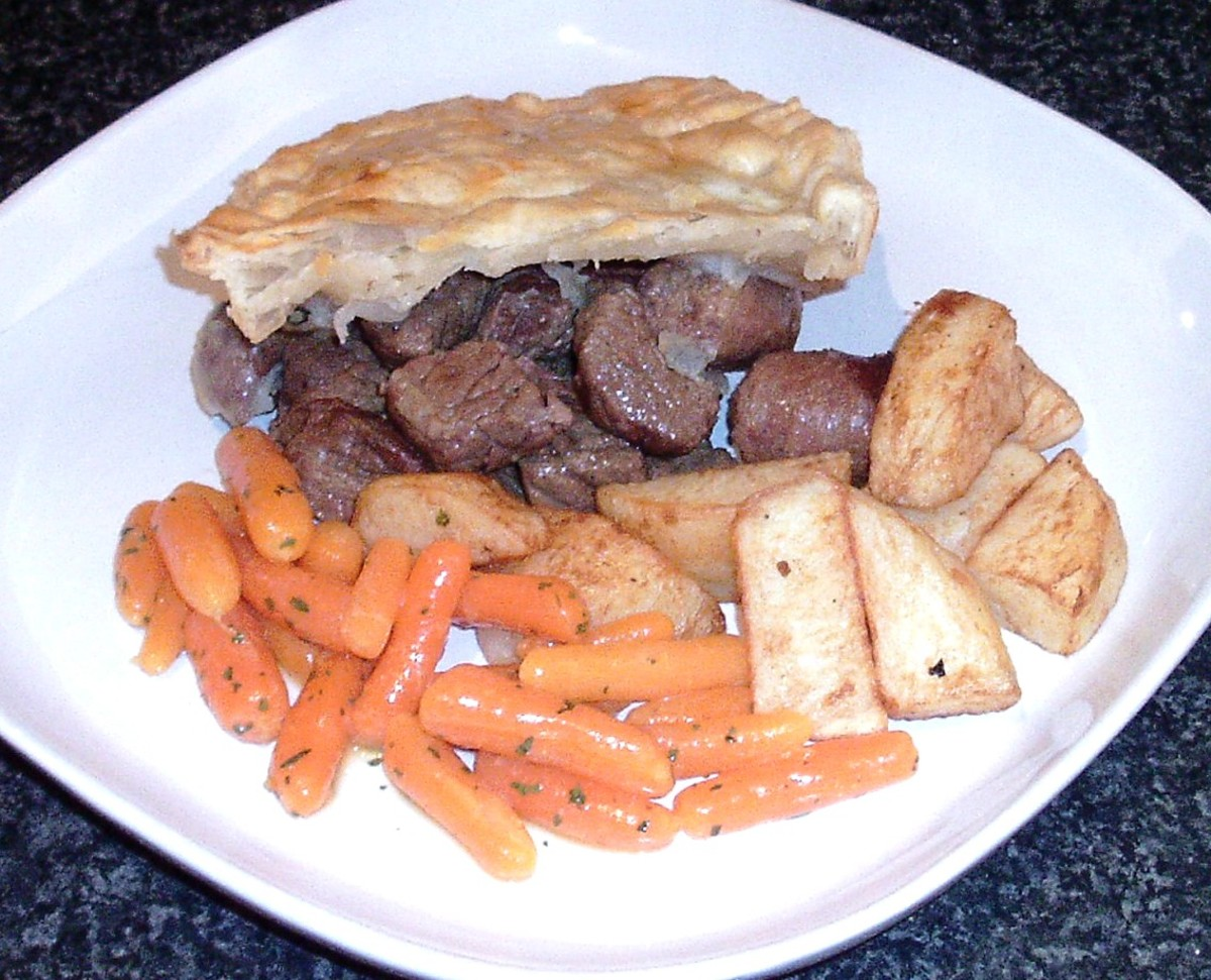 Succulent beef steak and venison sausages in a puff pastry pie with potatoes and carrots
