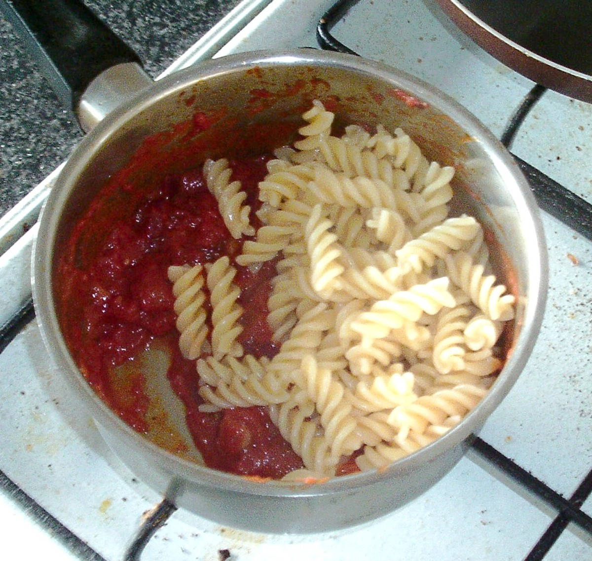 Fusilli pasta is added to tomato sauce