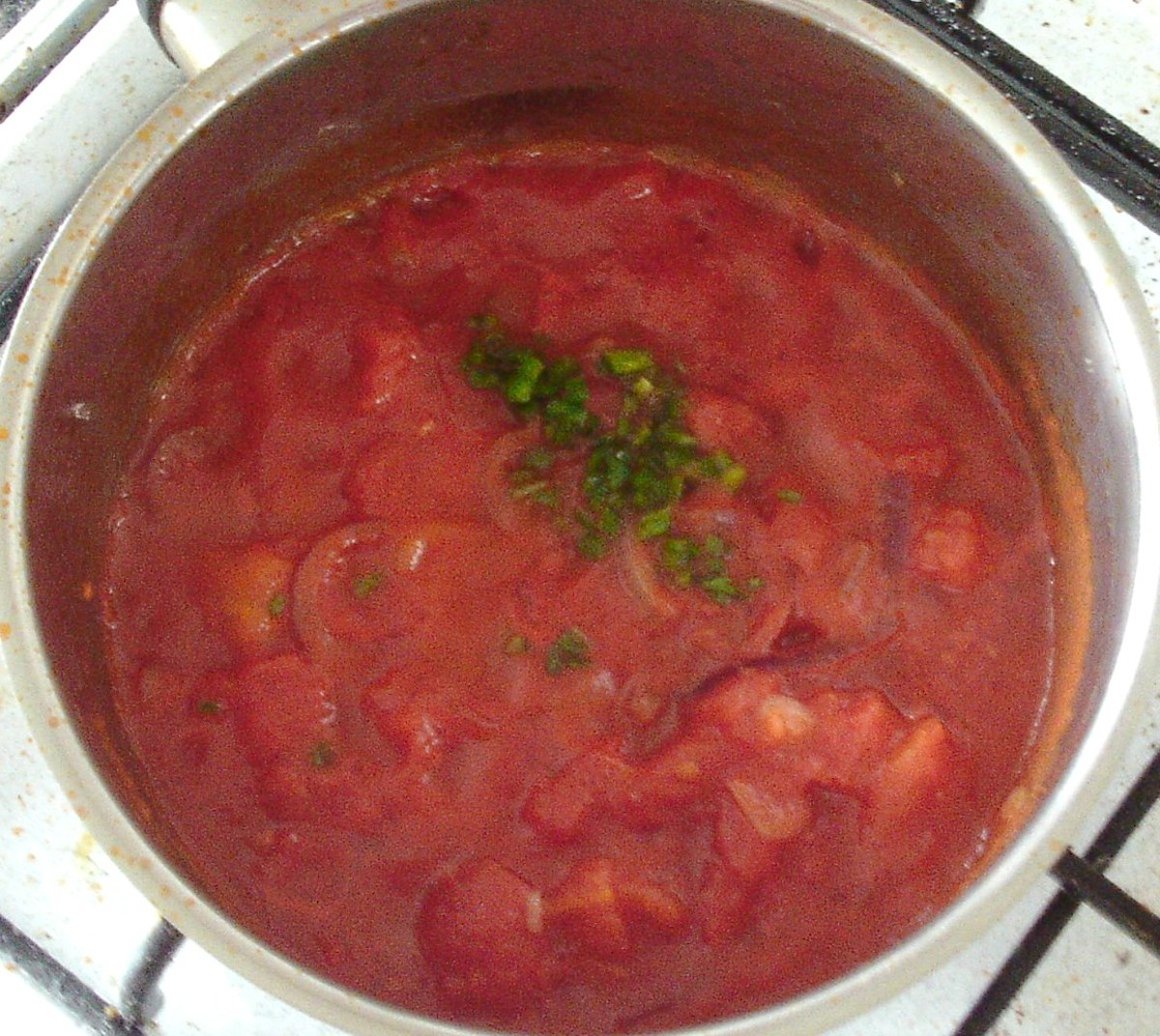 Canned tomatoes and chilli are added to softened onion