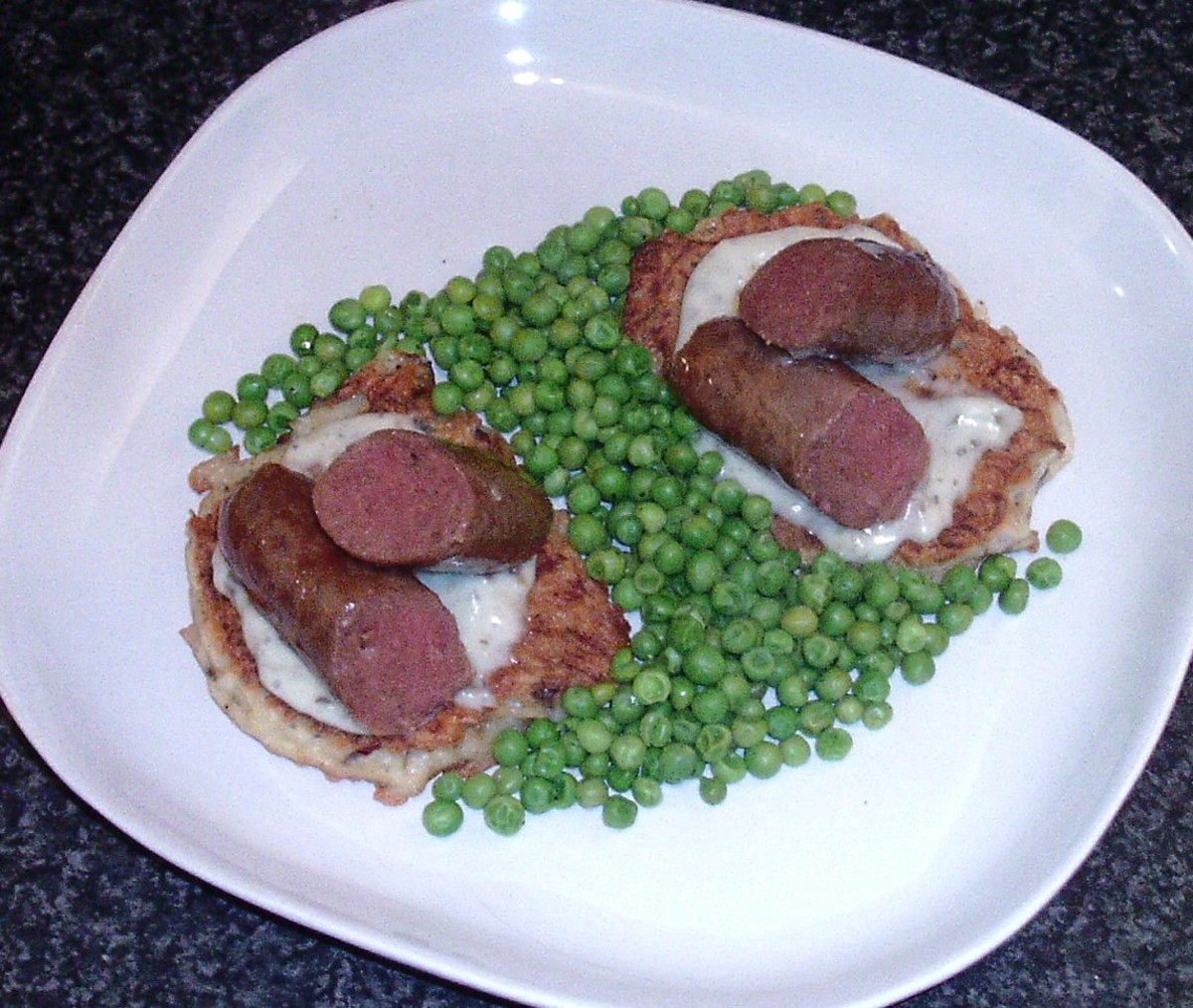 Venison sausages are served on potato cakes spread with horseradish sauce
