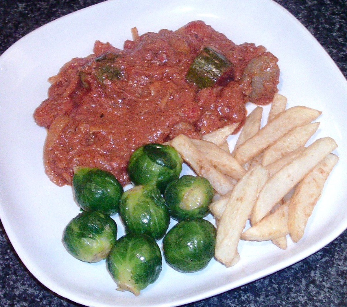 Venison sausages, lambs liver and Mediterranean vegetables stew is served with Brussels sprouts and chips