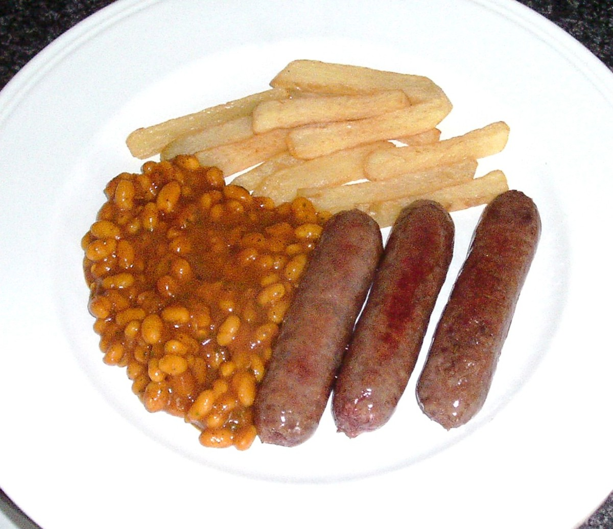 Venison sausages, chips and beans are plated