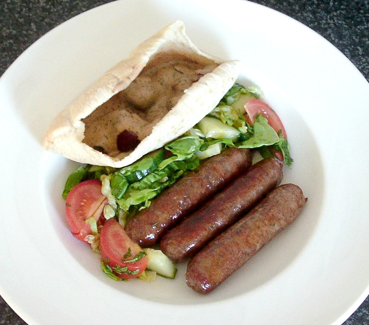 Venison sausages with mushrooms in spicy sauce pitta pocket and salad