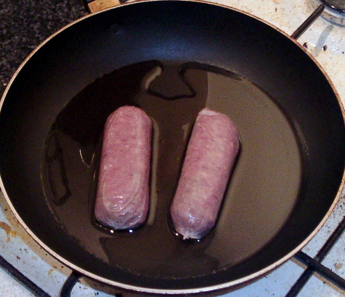 Venison sausages are added to warm oil in a non-stick frying pan.