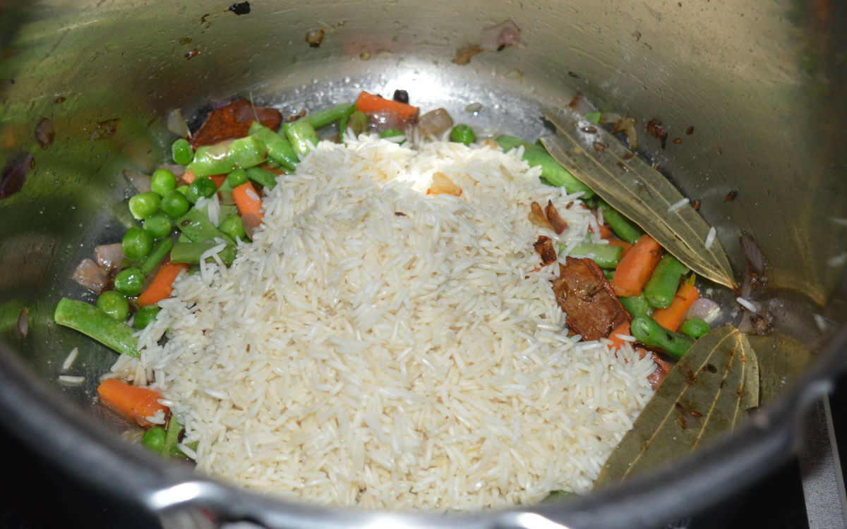 Step five: Throw in soaked rice. Continue stir-cooking for another 3 minutes.