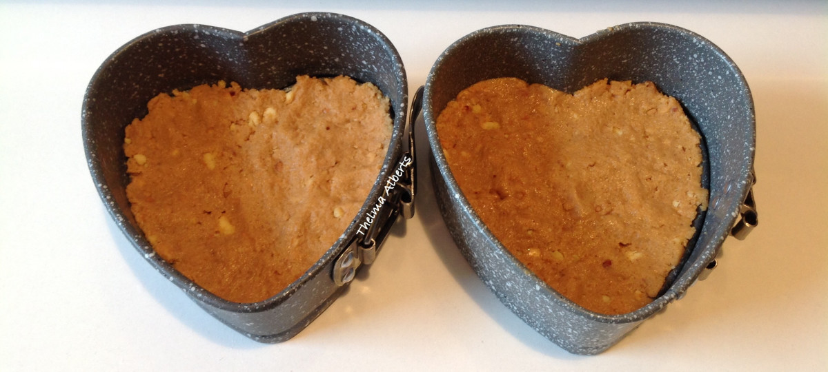 Biscuits and peanut butter paste inside the heart springform.