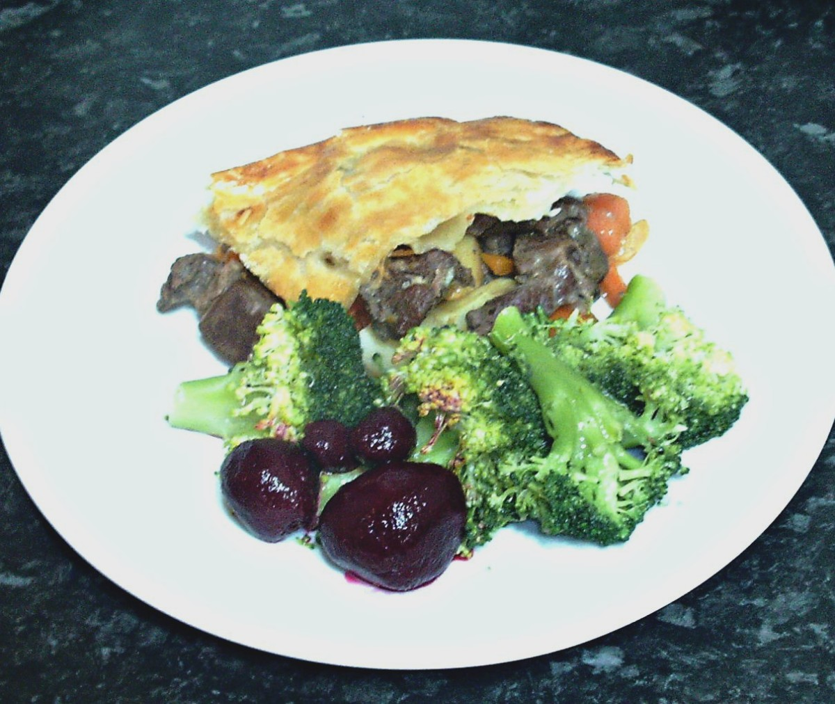 Drained broccoli and pickled beets are plated with alpaca pie