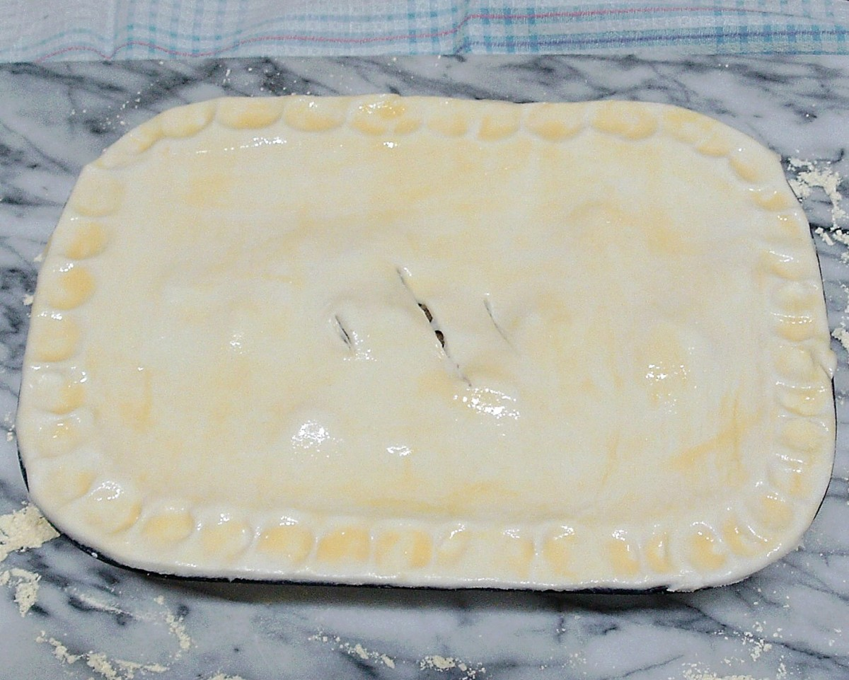 Pastry is glazed and pie is ready for the oven