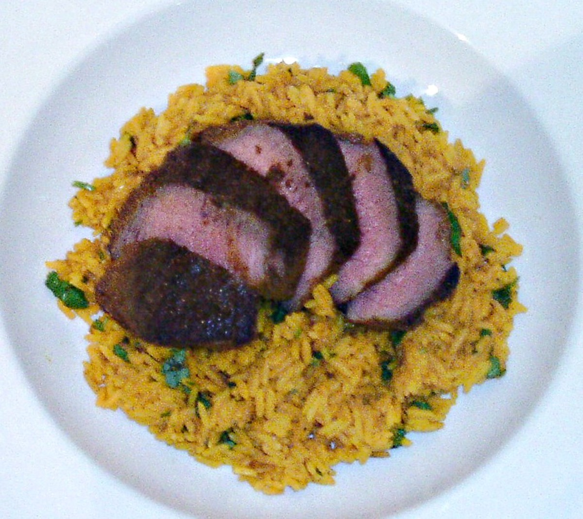 Sliced ostrich fillet steak is arranged on turmeric rice