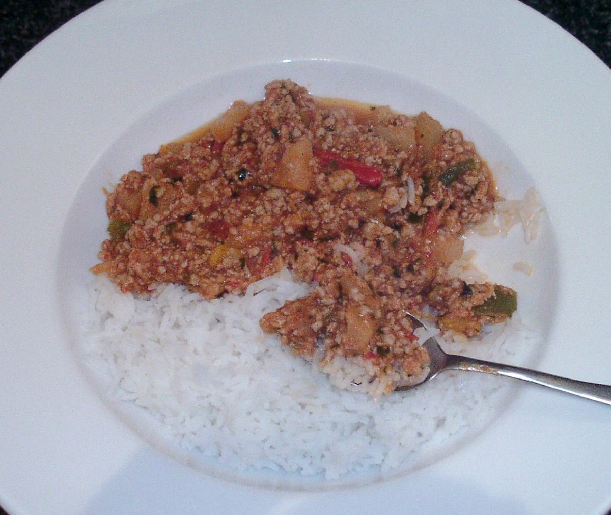 Enjoying sweet and spicy pork, peppers and pineapple with fried rice