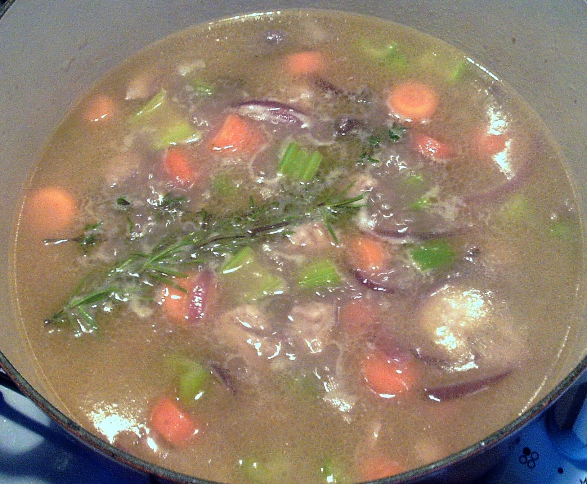 Chicken stock and fresh herbs are added to cooking pot