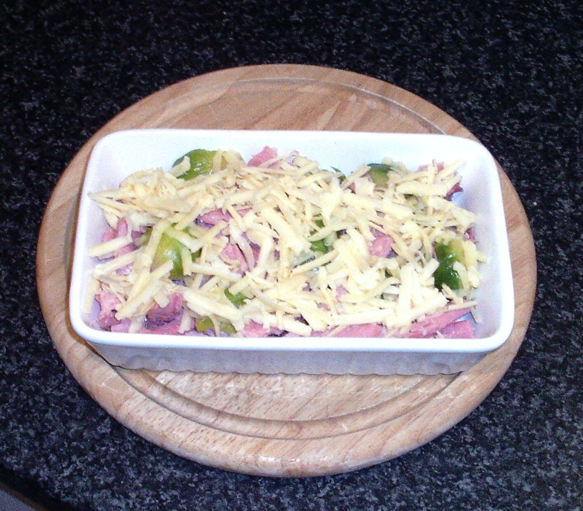 Cheese scattered over ham and sprouts