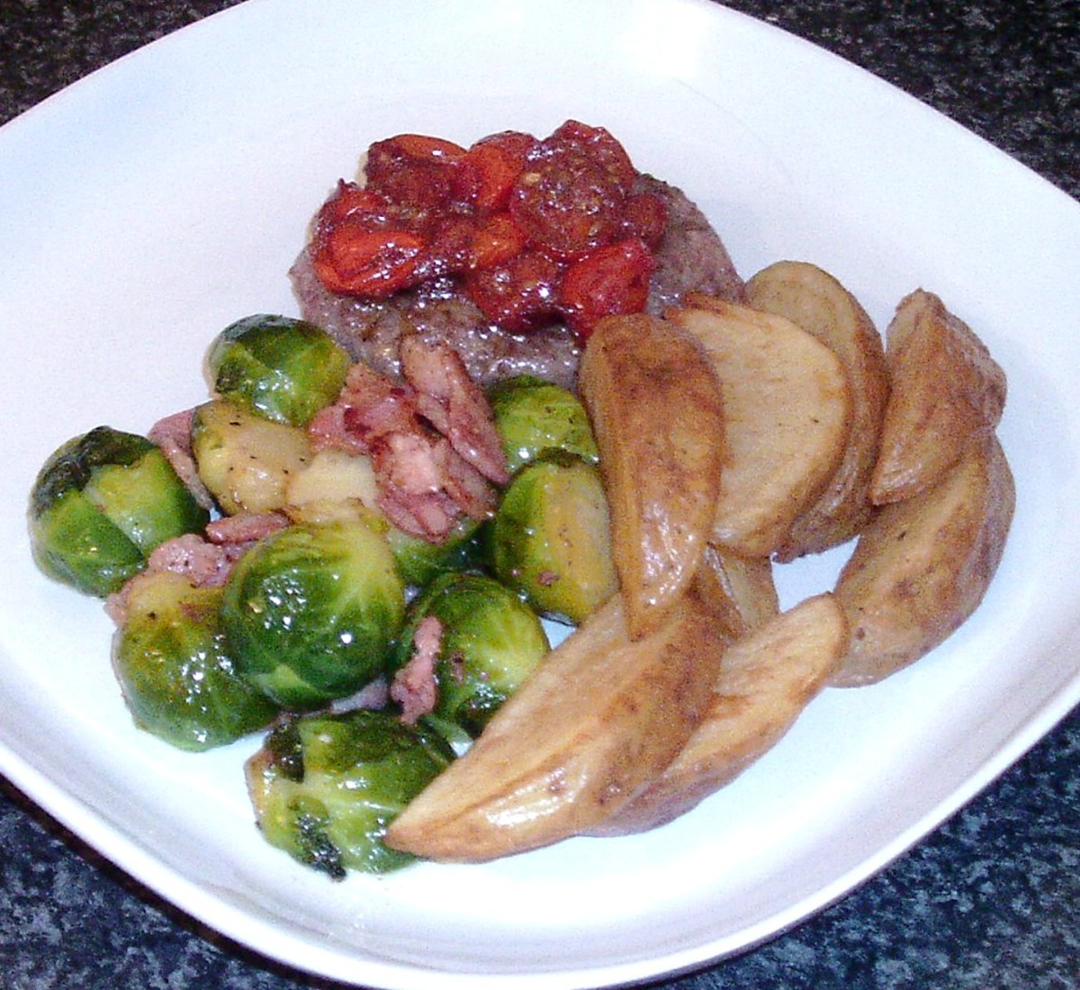 Wild boar and apple burger, topped with homemade tomato chutney, is served with Brussels sprouts and bacon and homemade wedges