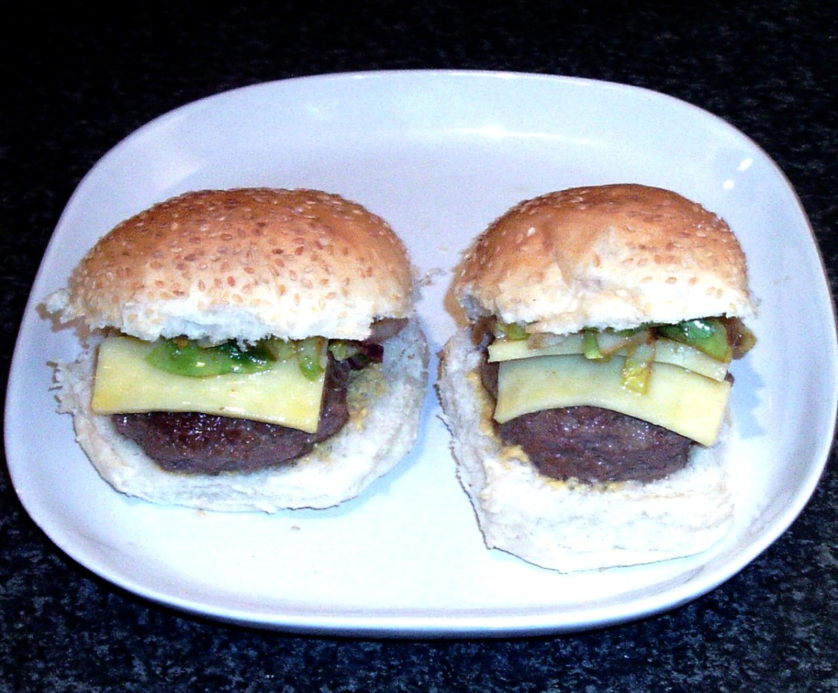 Cheeseburgers are topped with fried shredded sprouts and onion