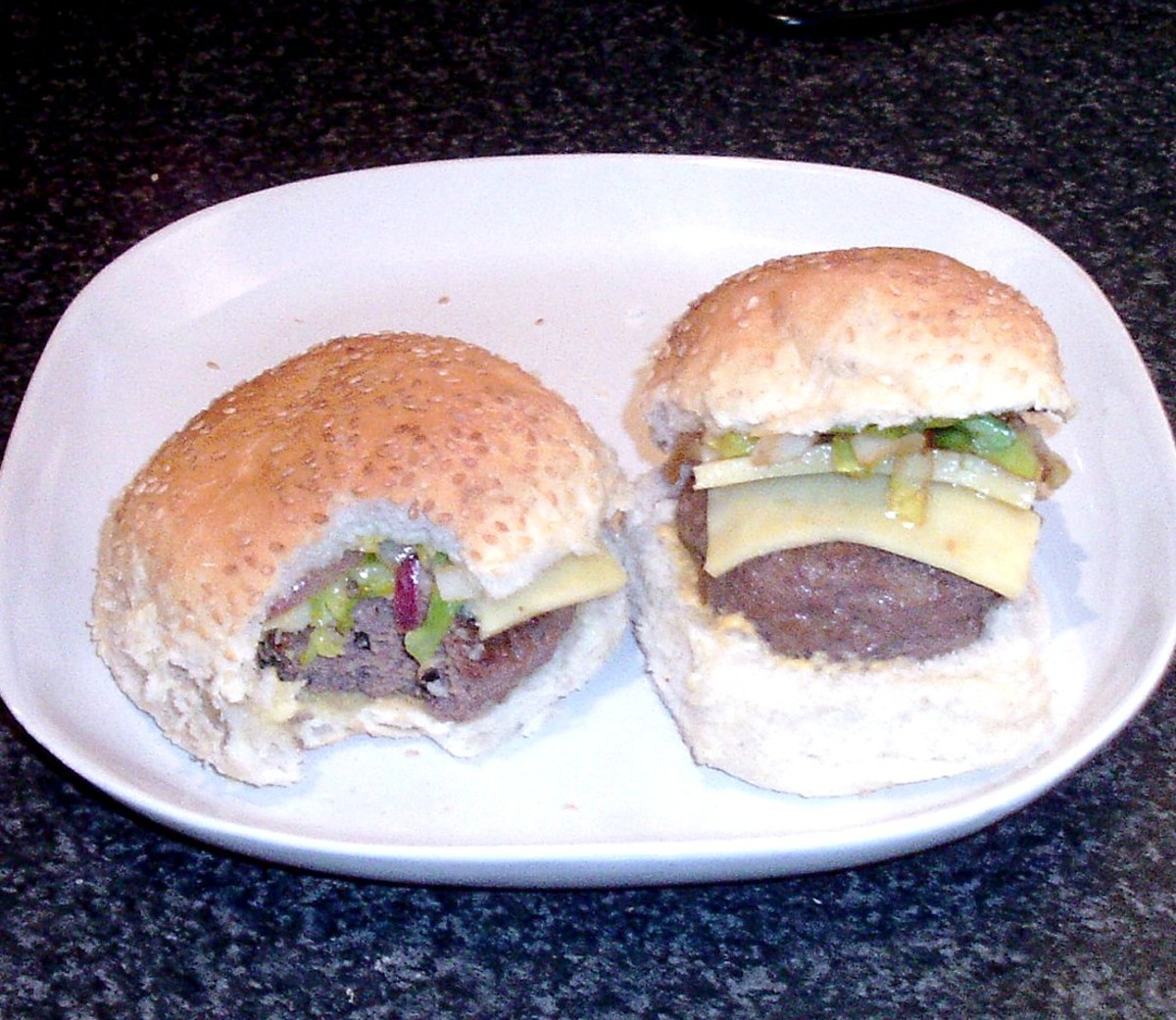 Biting in to cheeseburger with fried sprouts and onion