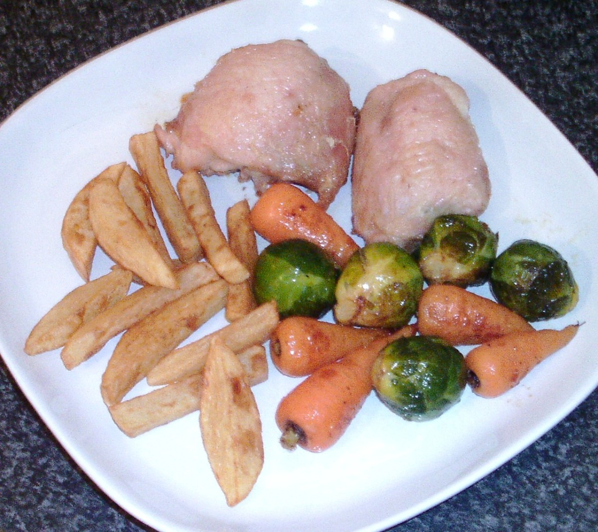 Roast chicken thighs with sprouts and carrots served with homemade chips