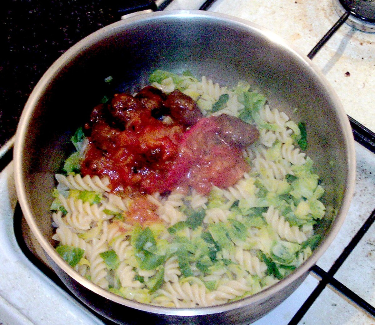 Meatballs in salsa are added to pasta and sprouts