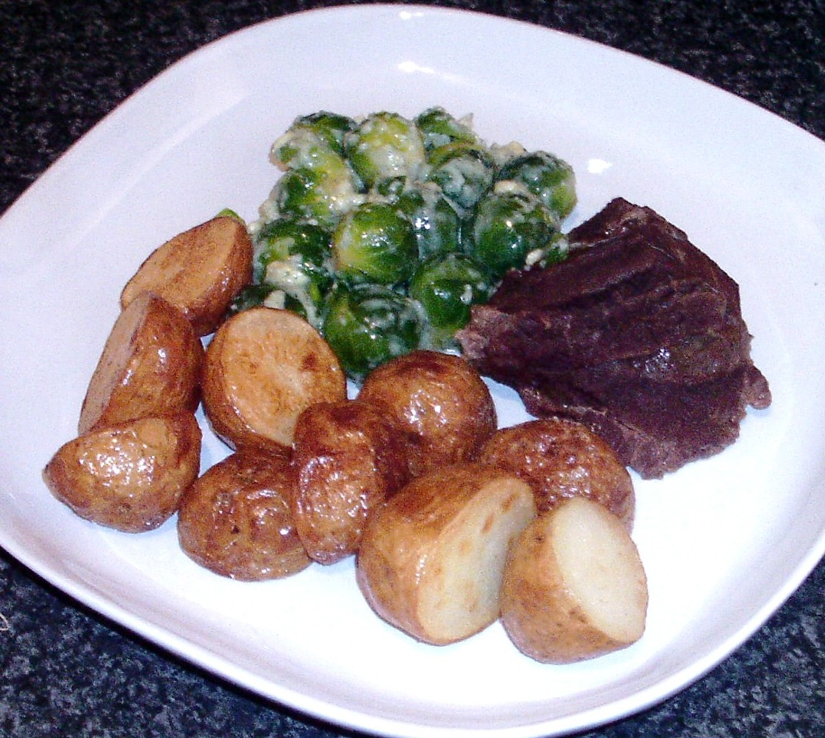 Slow stewed ox cheek with Brussels sprouts in blue cheese and deep fried new potatoes