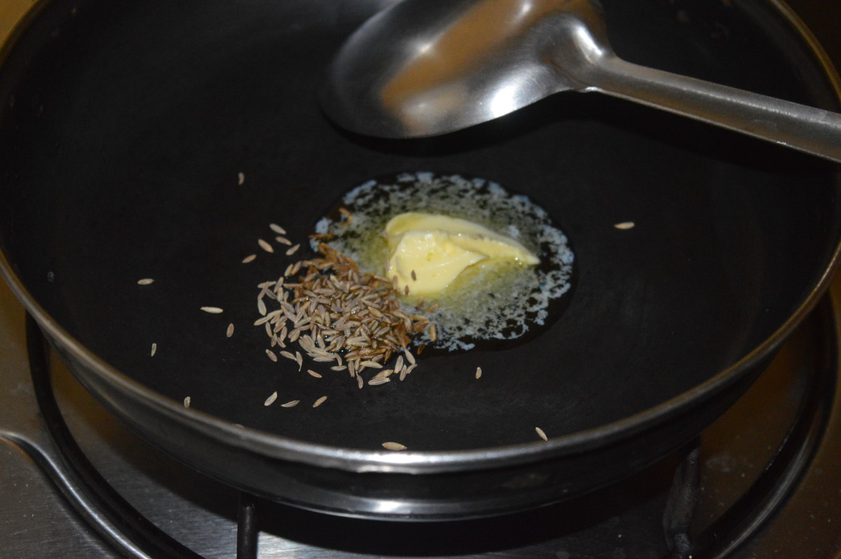Step four: Heat butter in a deep-bottomed pan. Add cumin seeds. Let them sizzle.