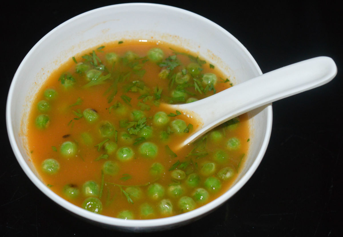 Step nine: Pour this soup equally into four bowls. Add equal amount of cooked green peas to each bowl. Garnish this soup with freshly chopped green coriander leaves.