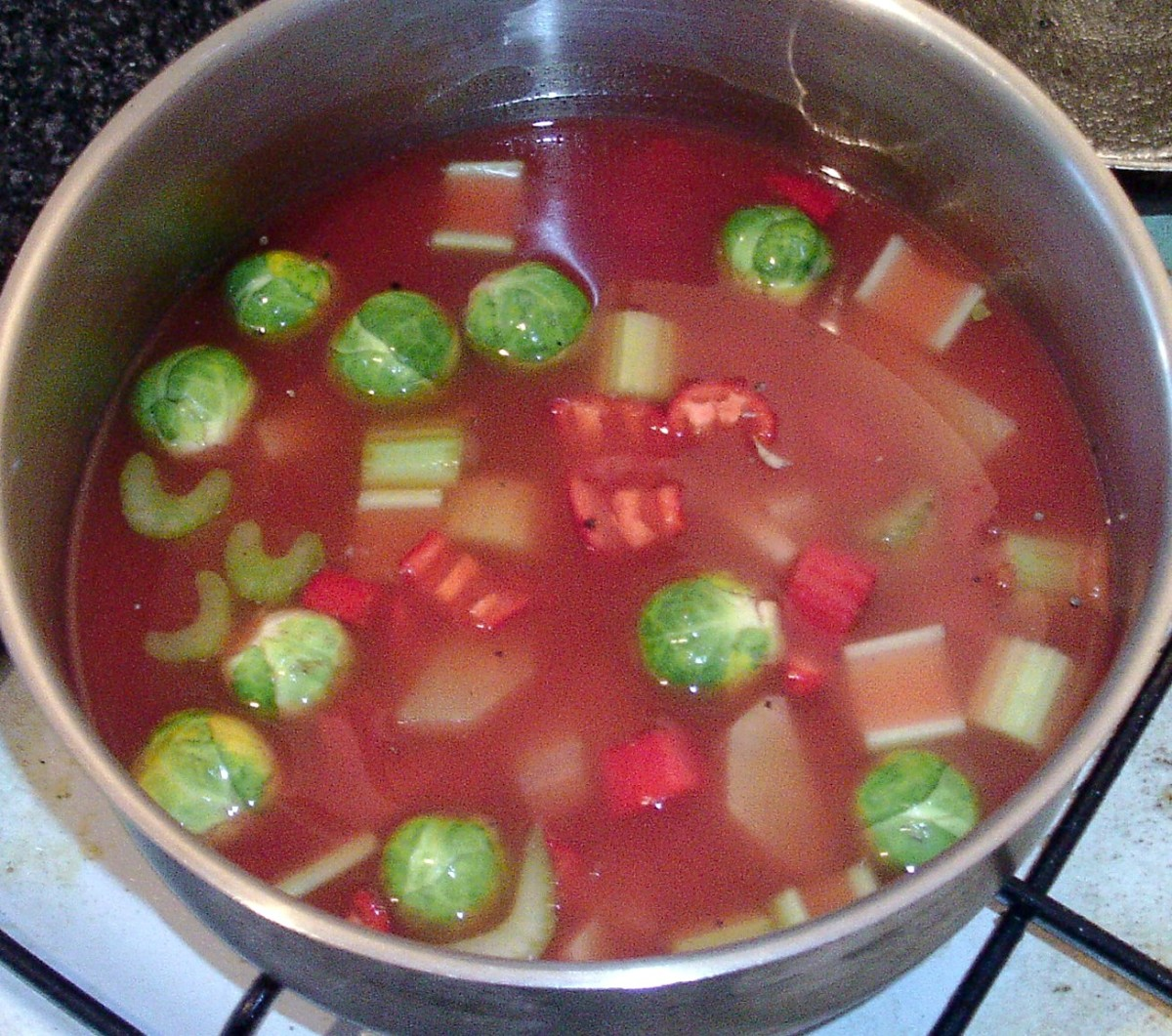 Stock is added to soup pot and ingredients are stirred together