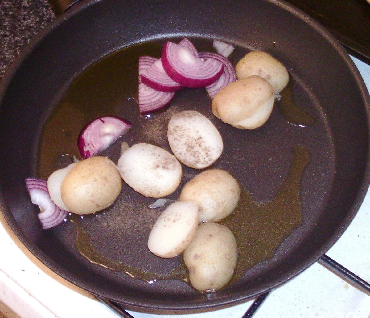 Potatoes and onions are added to hot pan and seasoned