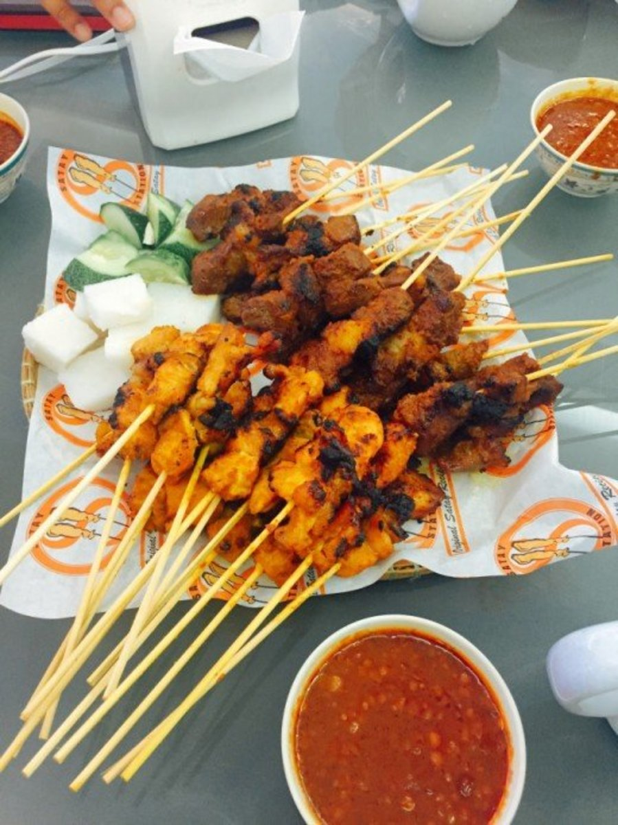 Authentic chicken and beef satay served with peanut sauce, nasi impit, and sliced cucumbers.