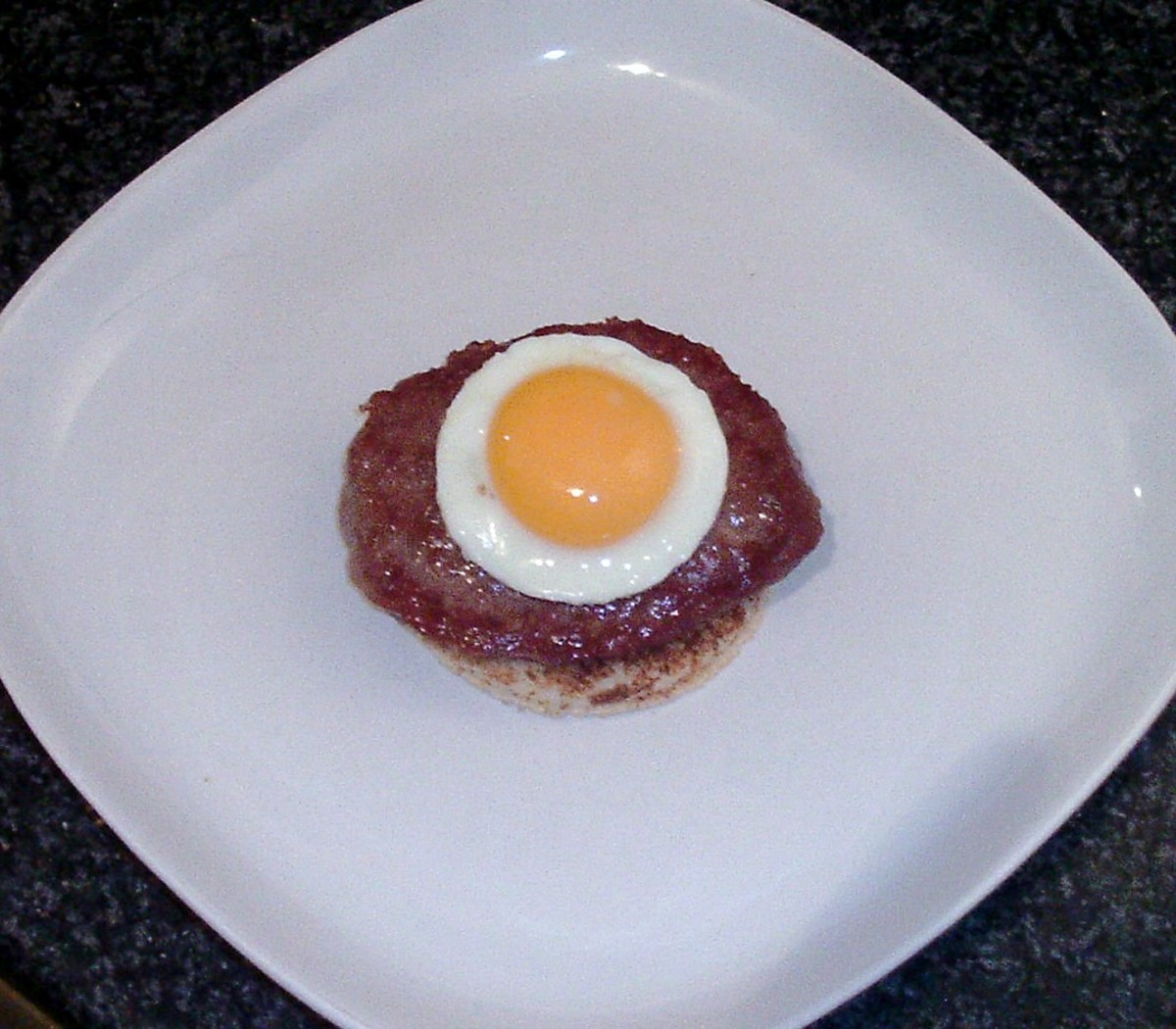 Fried egg circle is laid on top of burger