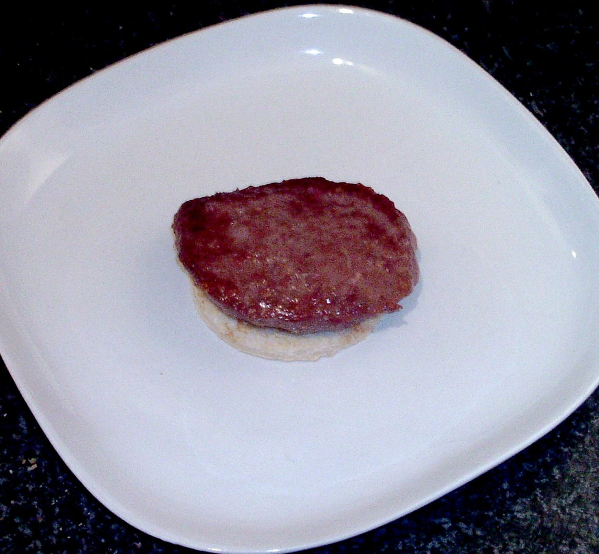 Rested blue beef burger is laid on top of toast circle