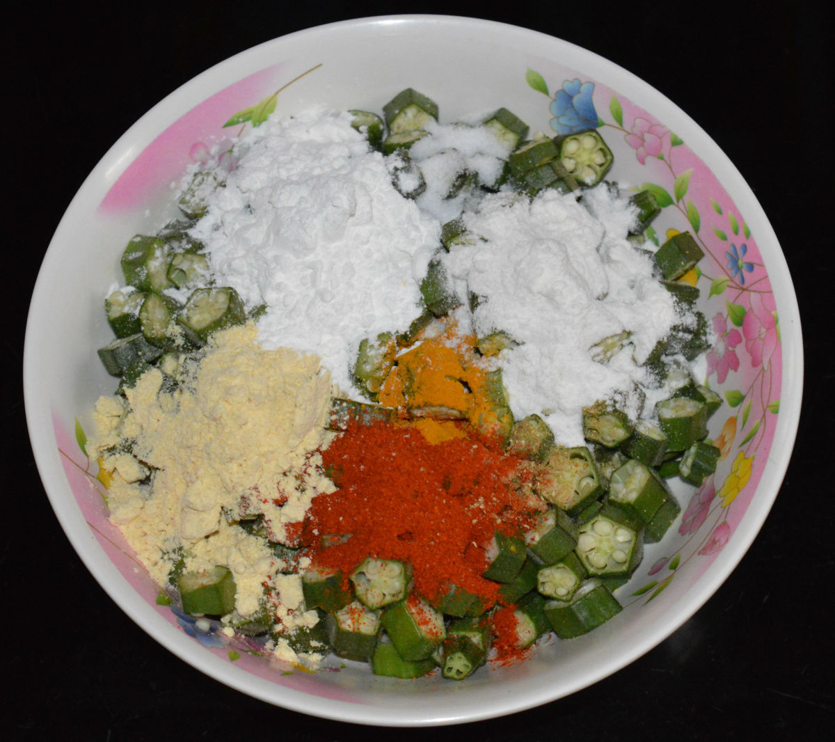 Step 2: Add corn flour, gram flour, rice flour, turmeric powder, red chili powder, chopped green chilies (optional), coriander powder, and salt.