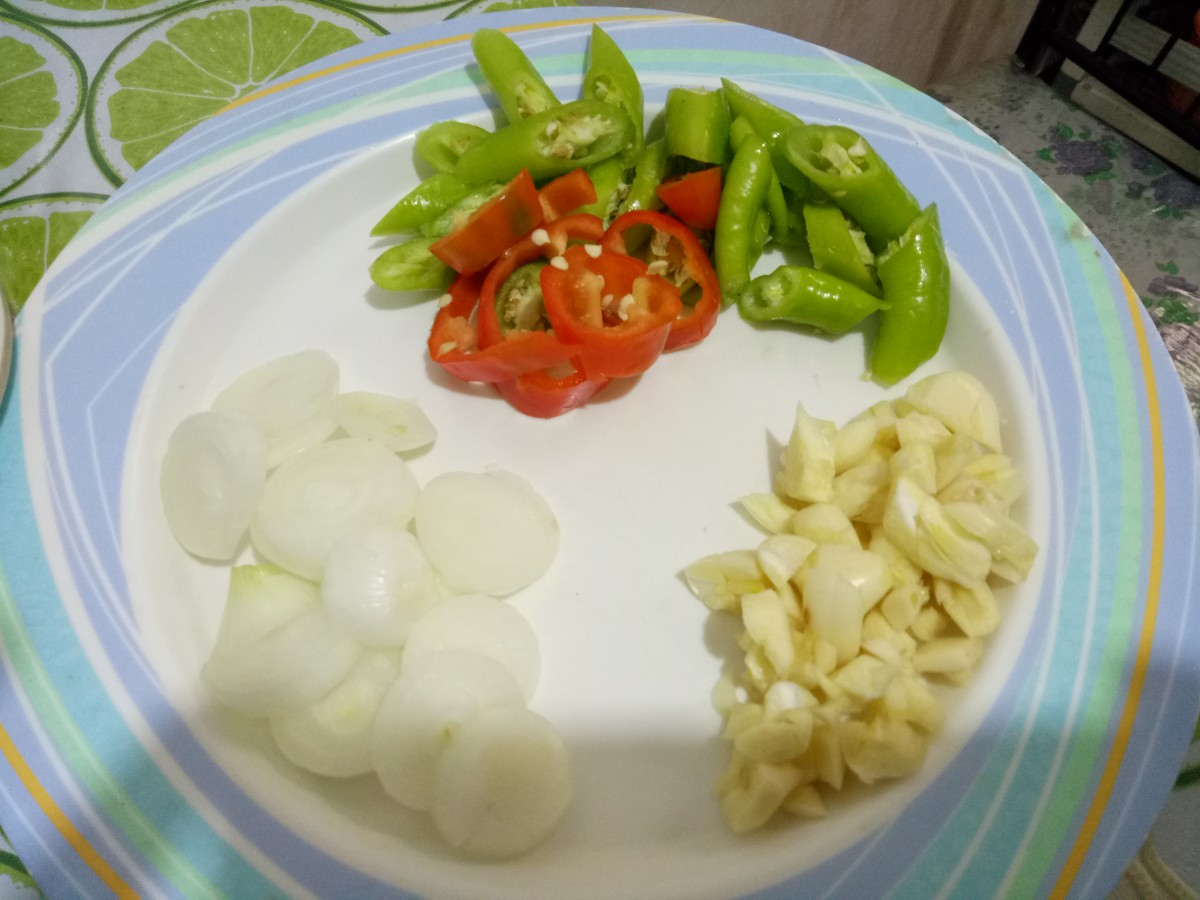 Slice the onion, garlic, bell pepper, and green chilies