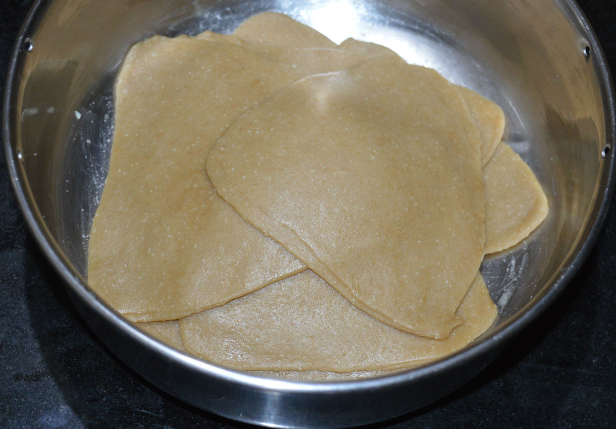 Step four: Take a ball. Roll it to make a disc. Apply a bit of ghee  on the surface. Fold it. Once again, apply ghee. Fold it. Roll it to get a triangular cake. Don't use flour for rolling . Instead, use oil or ghee.