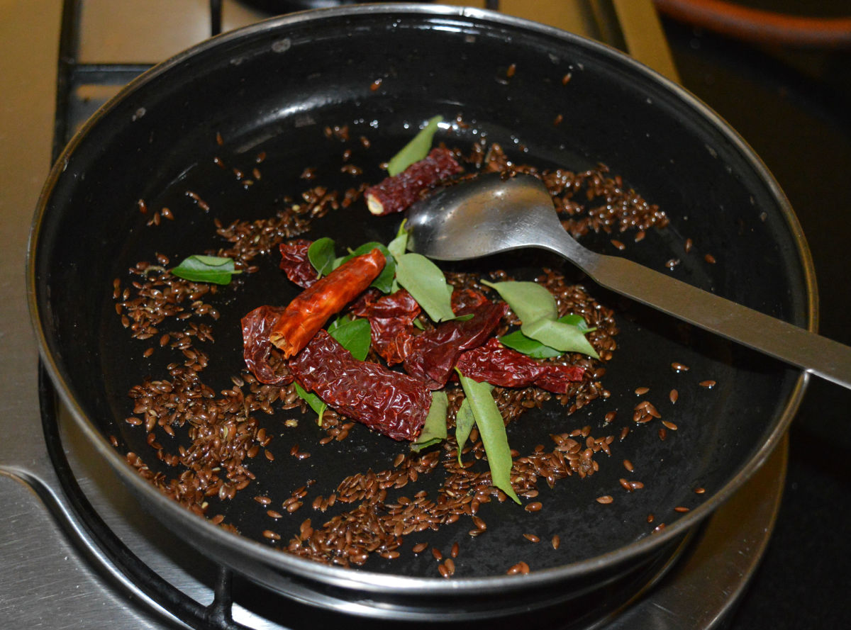 Step two: Throw in curry leaves and broken dry red chilies. Saute for 10 seconds. Turn off the heat.
