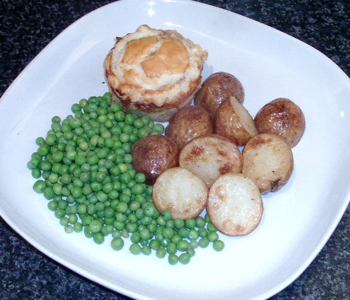 Venison and red wine gravy mini puff pastry pie plated for service with roast potatoes and peas