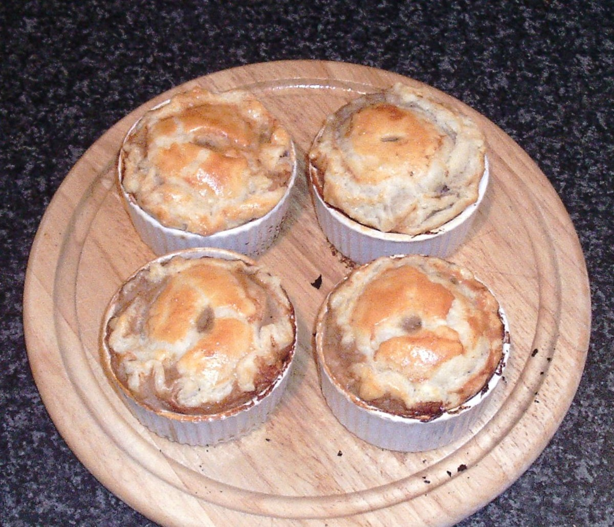 Baked venison and red wine gravy pies are removed from the oven