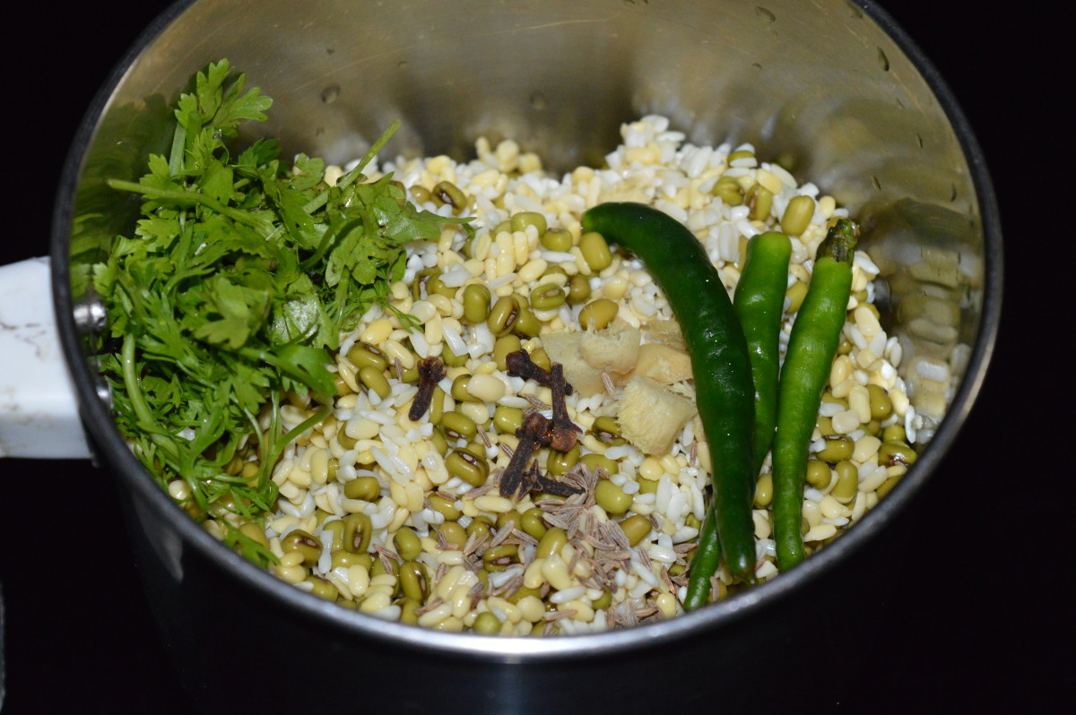 Step two: Strain the water. Collect it in a bowl. Use it for grinding. Put mung beans, moong dal, and rice to a mixer or grinder. Add ginger, green chilies, salt, cloves, and fresh coriander.