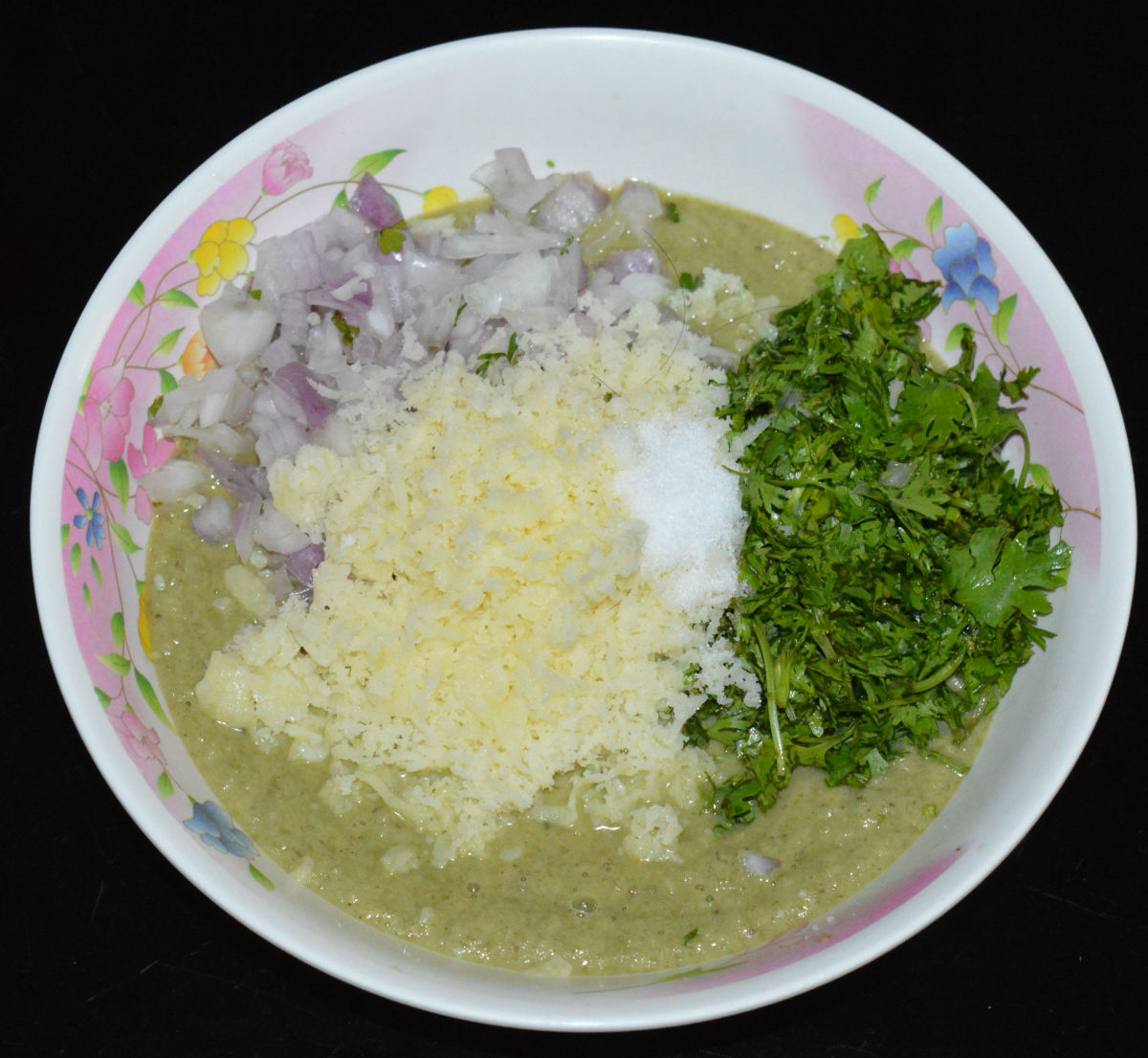 Step two: Put the batter in a mixing bowl. Add grated cheese, chopped coriander, chopped onions, and salt. Mix well.