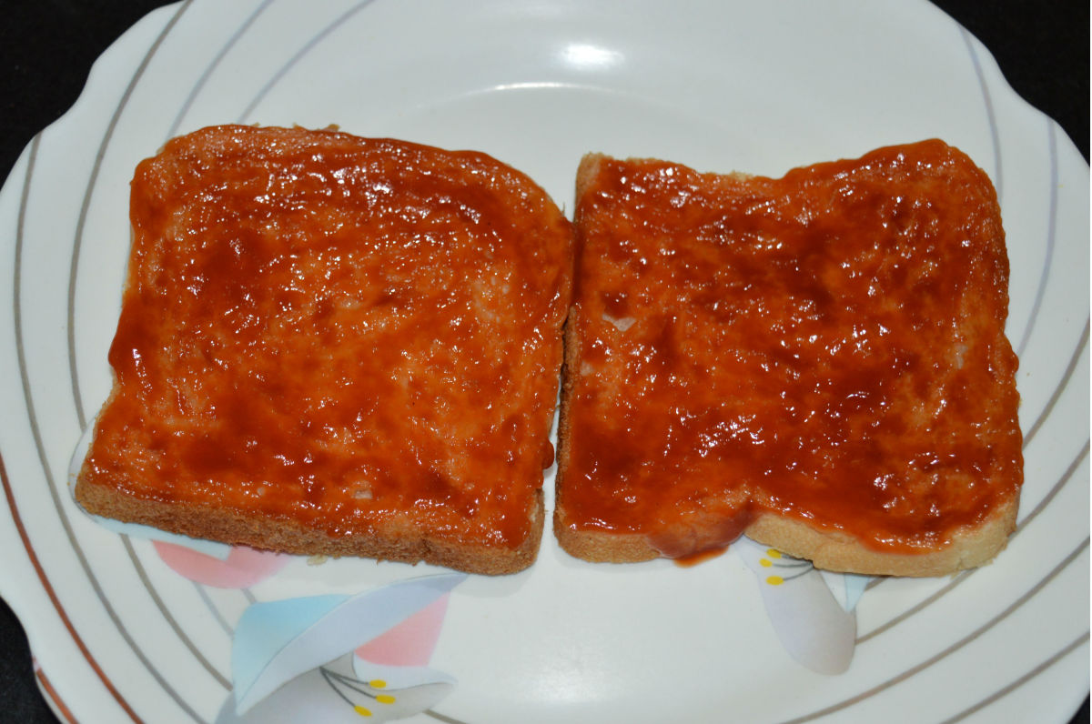Step three: Take two bread slices. Thinly spread tomato sauce on them.