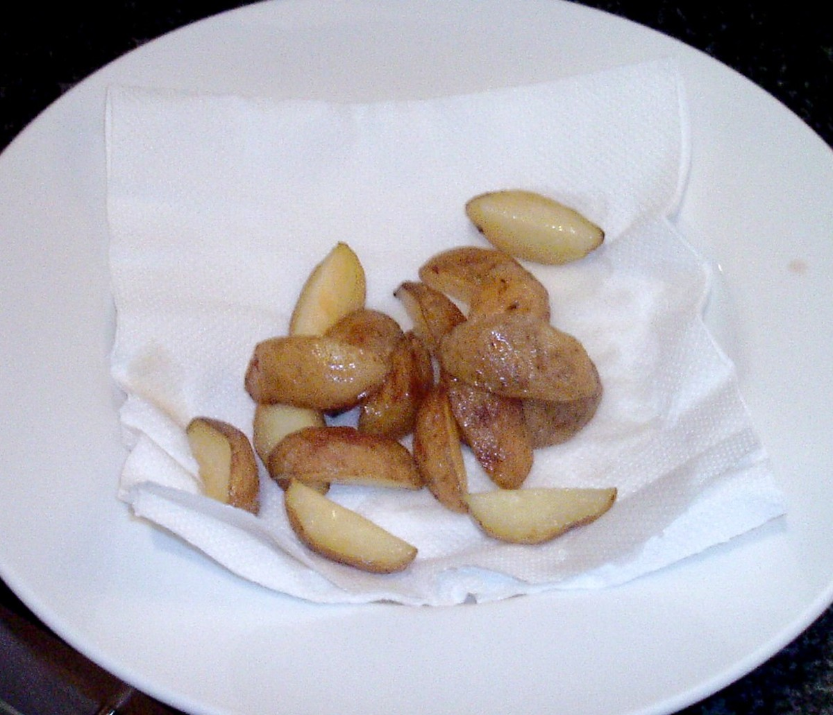 Roast potatoes are drained on kitchen paper