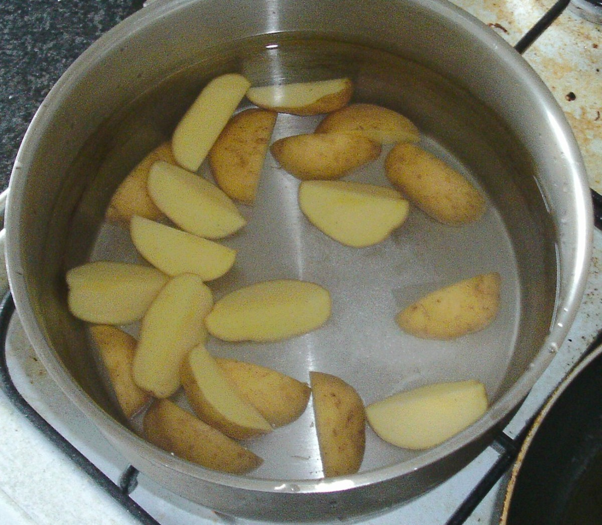 Quartered potatoes are added to cold salted water and put on to cook