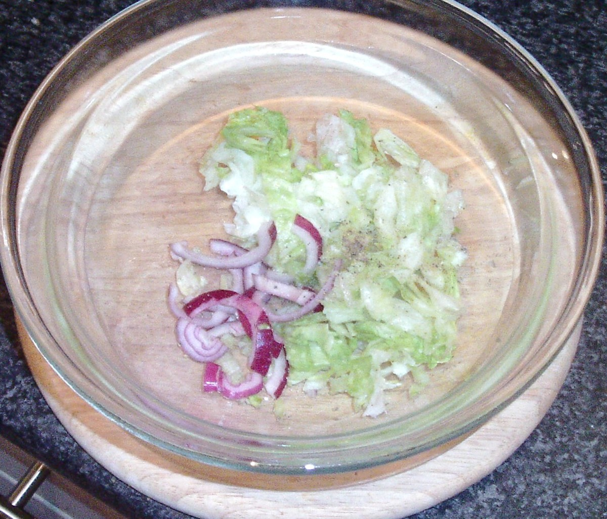 Lettuce and onion is seasoned and tossed to combine